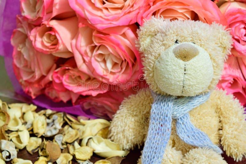 Nallebjörnen sitter med en bukett av rosor royaltyfria bilder