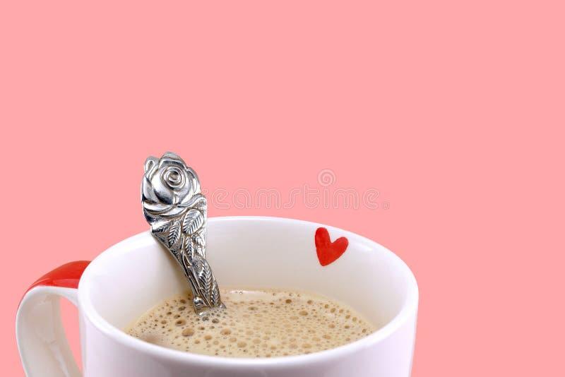 Nam het close-up kleine rode hart op ceramische koffiekop en bloem gevormde zilveren die lepel op roze achtergrond wordt geïsolee stock afbeeldingen