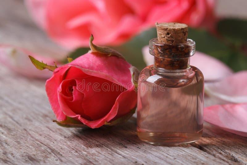 Nam olie in een glasfles en roze bloemen dichte omhooggaand toe stock fotografie