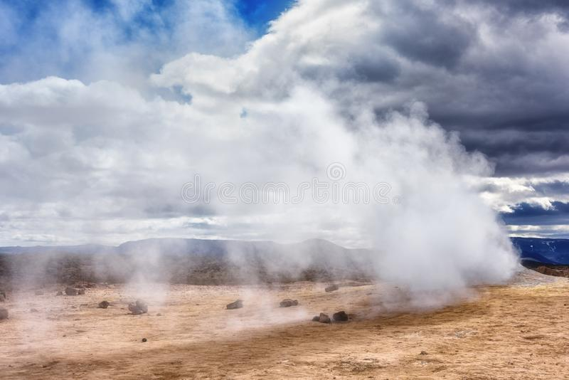 Namafjall Hverir geothermal area in Iceland. Stunning landscape of sulfur valley with smoking fumaroles and blue cloudy sky. Travel background, tourist stock photo