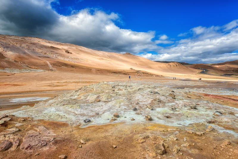 Namafjall Hverir geothermal area in Iceland. Stunning landscape of sulfur valley with smoking fumaroles and blue cloudy sky. Travel background, tourist stock images