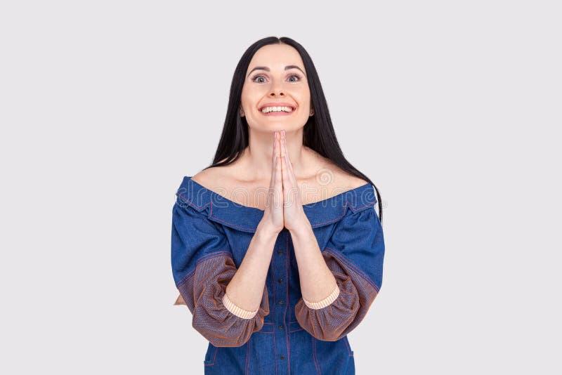 Namaste, может мир быть с вами Портрет счастливой выглядящей дружелюбн молодой женщины с темными волосами в джинсах одевает, держ стоковые фото