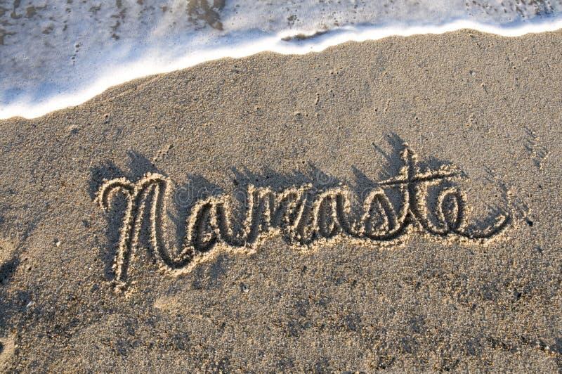 Namaste geschrieben in den Sand lizenzfreie stockbilder