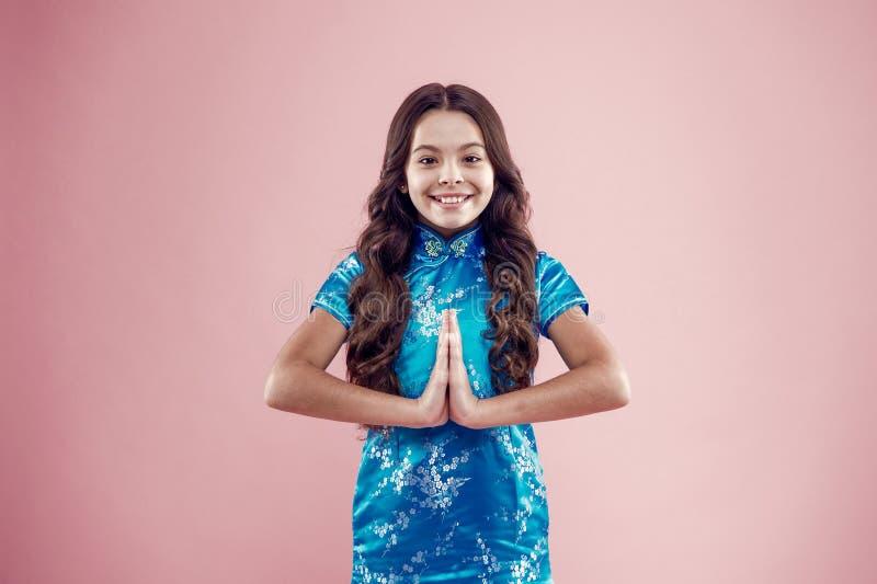 Namaste Oosterse cultuur Een klein meisje draagt traditionele oosterse kleding op een roze achtergrond Algemeen gebruikte gebaren royalty-vrije stock foto's