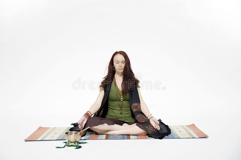 Namaste Yoga Woman White Background. Beautiful red haired yogini woman photographed on a white background. She is sitting on a yoga blanket in meditation with royalty free stock photography