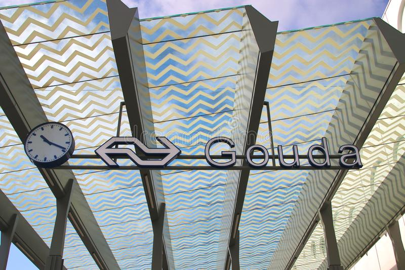 Name sign of Gouda on the entrance of train station  with solar panels in the glass roof. stock image