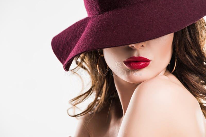 namiętna kobieta z czerwonymi wargami chuje oczy pod Burgundy kapeluszem obrazy royalty free