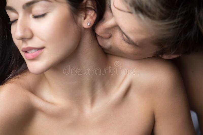 Namiętna mężczyzna całowania kobieta na szyi cieszy się foreplay zdjęcia royalty free