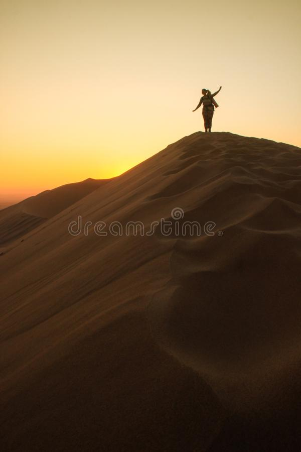 Namib Desert, in the Namib-Nacluft National Park in Namibia. Sossusvlei. Young woman tourist with backpack stands on top royalty free stock image