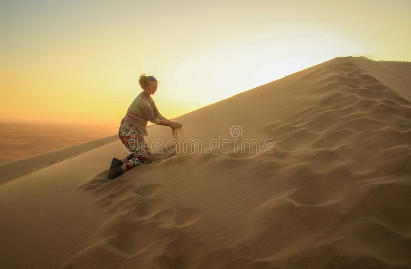 Namib Desert, in the Namib-Nacluft National Park in Namibia. Sossusvlei. Young woman tourist playing with sand stock images