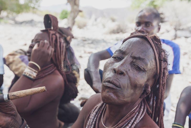 NAMIBE/ANGOLA - 28 de agosto de 2013 - retrato da mulher idosa africana que pertence a um tribo que fuma com tubulação fotografia de stock royalty free