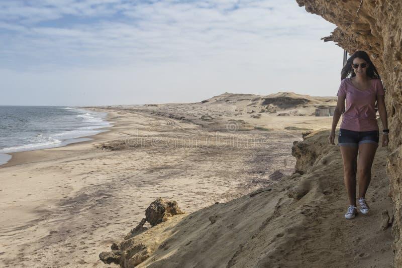 NAMIBE/ANGOLA 2 DE NOVEMBRO DE 2018 - a moça anda em um trajeto da garganta pela praia selvagem de Namibe angola África imagem de stock royalty free