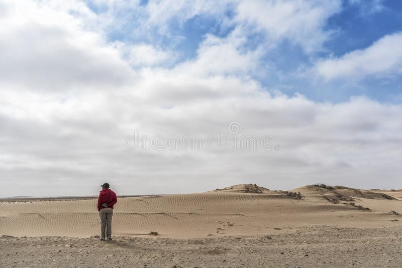 NAMIBE/ANGOLA - 26OCT2017 - Man looking at the immensity of the Namibe Desert. Africa. Angola. royalty free stock photography