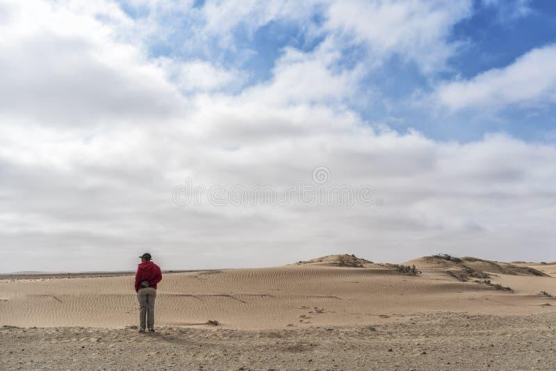 NAMIBE/ANGOLA - 26OCT2017 - Mens die de reusachtigheid van de Namibe-Woestijn bekijken afrika angola royalty-vrije stock fotografie