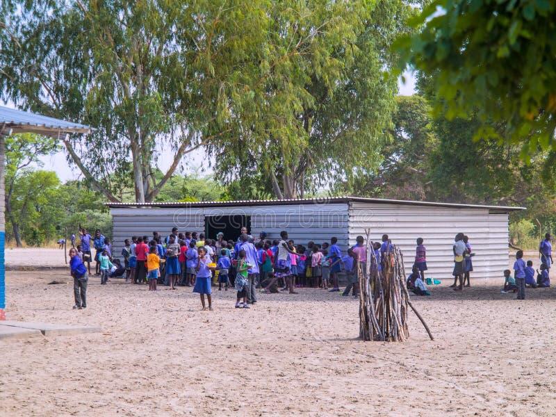 NAMIBIA Kavango, OKTOBER 15: Namibiska skolbarn som väntar på en lunch Kavango var regionen med det högsta armodet arkivbild