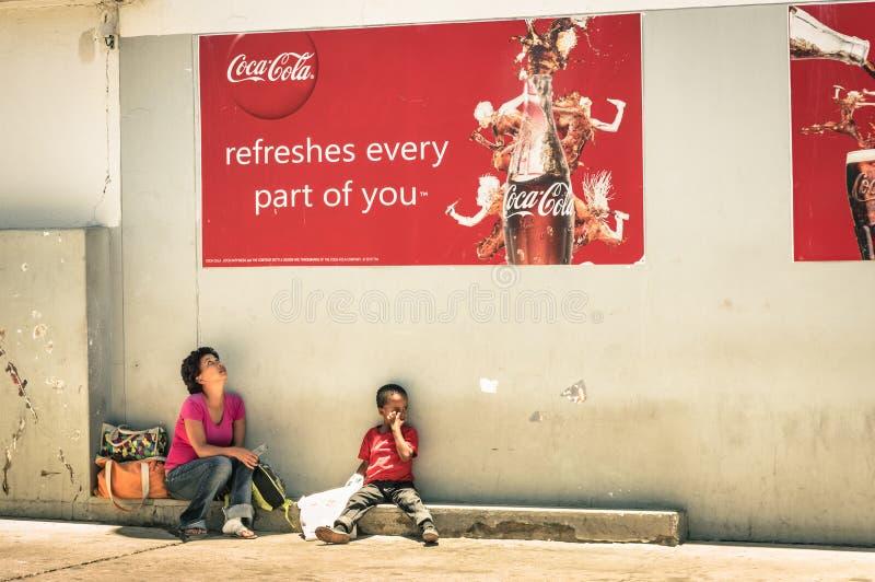 Namibian moeder en zoon onder Coca-colaaanplakbord stock foto's