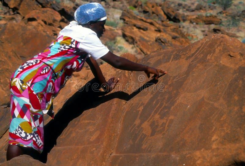 Namibisk kvinna som visar förhistoriska carvings arkivbild