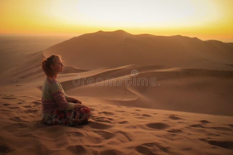 Namibwoestijn, in het Nationale Park namib-Nacluft in Namibi? Sossusvlei Jonge vrouwentoerist die yoga en ontspanning doen stock foto's