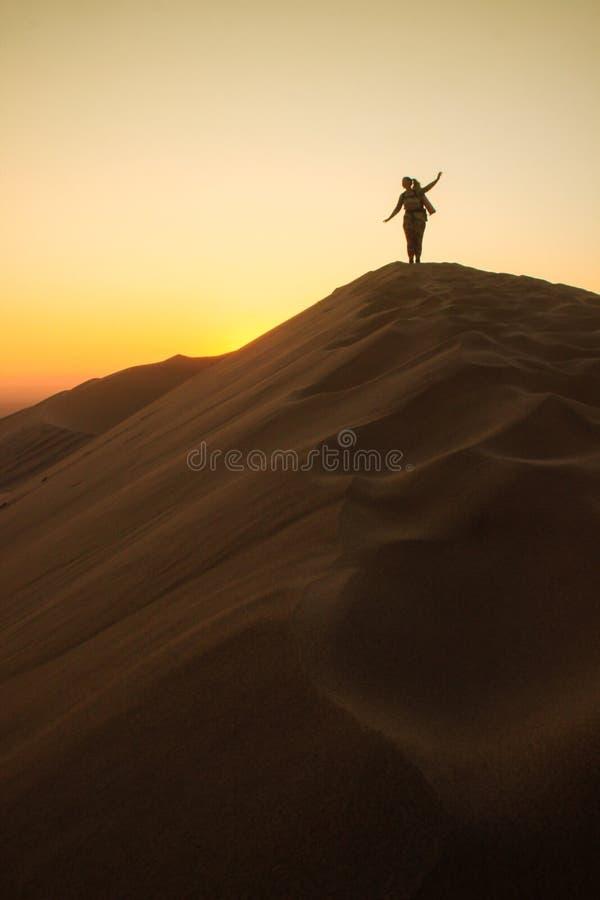 Namibwoestijn, in het Nationale Park namib-Nacluft in Namibi? Sossusvlei Jonge vrouwentoerist met rugzaktribunes op bovenkant royalty-vrije stock afbeelding