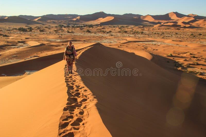 Namibwoestijn, in het Nationale Park namib-Nacluft in Namibi? Sossusvlei Jonge vrouwentoerist met rugzaktribunes op bovenkant royalty-vrije stock afbeeldingen