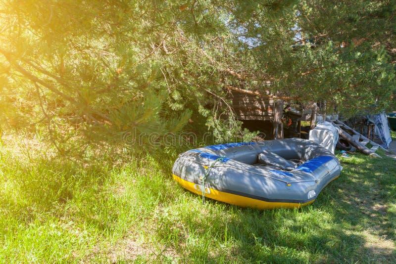 Namiotowy camping w cieniu pod drzewami z drewnianym domem i wielką nadmuchiwaną flisactwo łodzią blisko rzeki w Altai zdjęcie royalty free