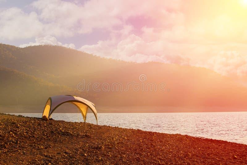 Namiotu schronienie na jeziornym brzeg przy zmierzchem - spokojna scena przenosi calmness i wolność fotografia royalty free