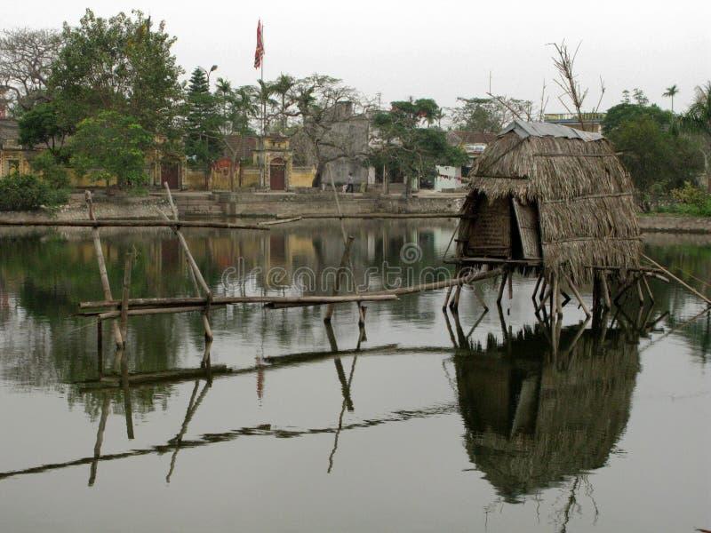 Namioty z pokrywającymi strzechą dachami rozkładają się na jeziorze zdjęcie stock