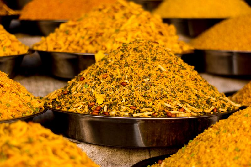 Namkeen in multiple steel plates. Yellow colored namkeen in steel plates kept at a shop in the daylight. Namkeen is a salty Indian snack royalty free stock photo