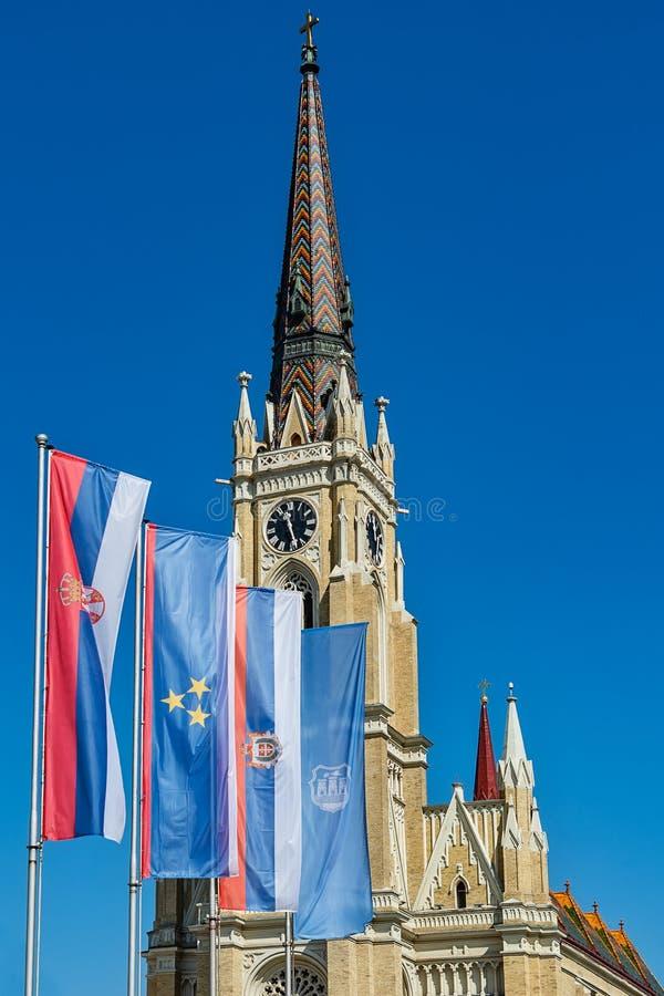 Namnet av Mary Church som är romerskt - katolsk församlingkyrka i Novi Sad, Serbien Flaggor av Serbien, Vojvodina och Novi Sad royaltyfri foto