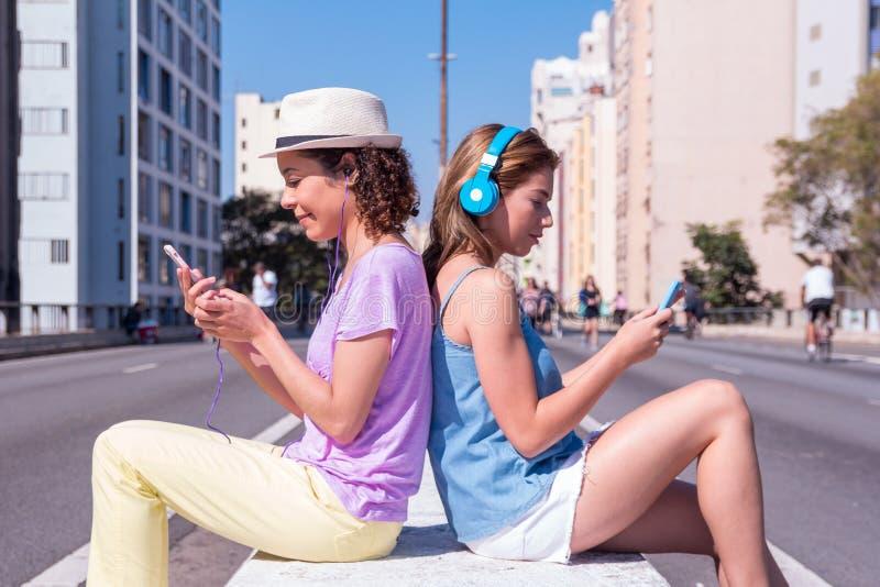 Namoradas da raça misturada de volta à parte traseira que escutam a música na rua sem tráfego Conceito da tecnologia, meio social imagens de stock