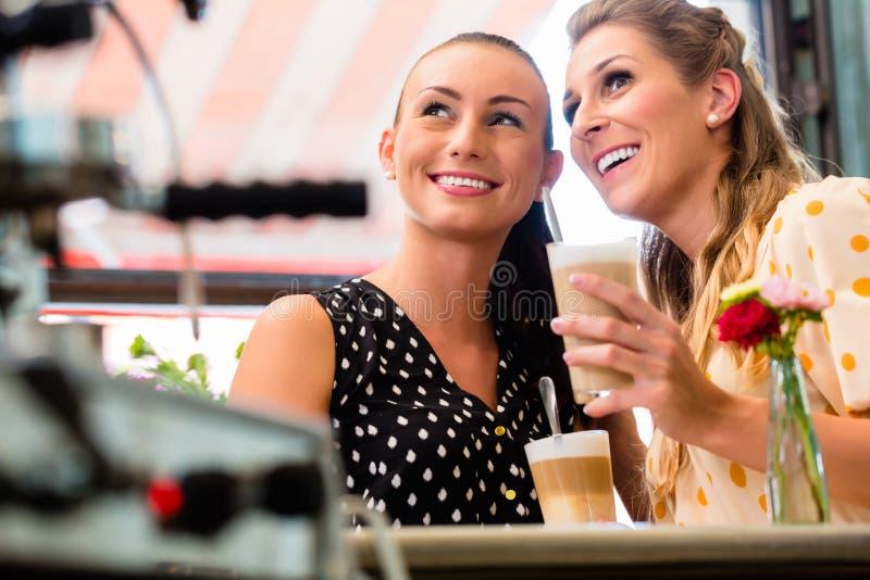 Namoradas que bebem o macchiato do latte na barra de café imagem de stock