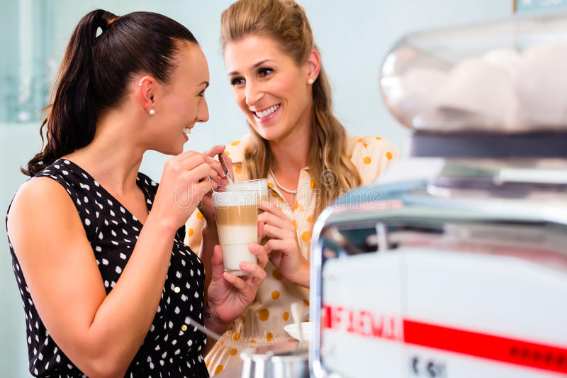 Namoradas que bebem o macchiato do latte na barra de café imagem de stock royalty free