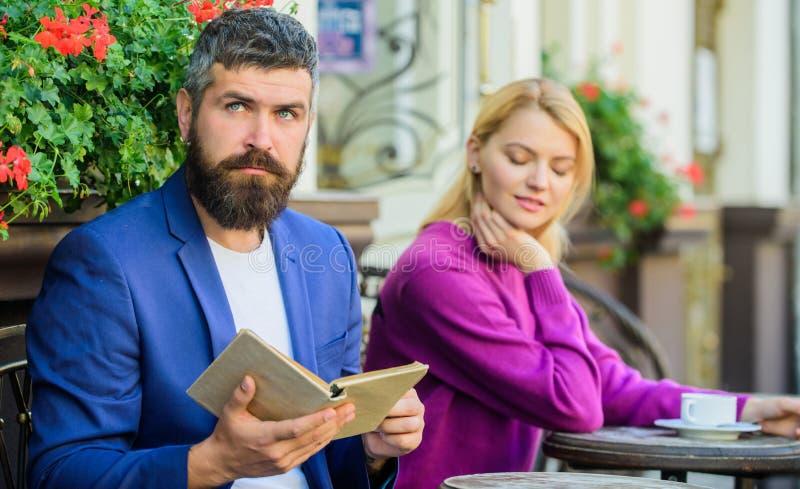 Namoradeira e data Povos da reunião com interesses similares O homem e a mulher sentam o terraço Achado do interesse comum da lit imagens de stock royalty free