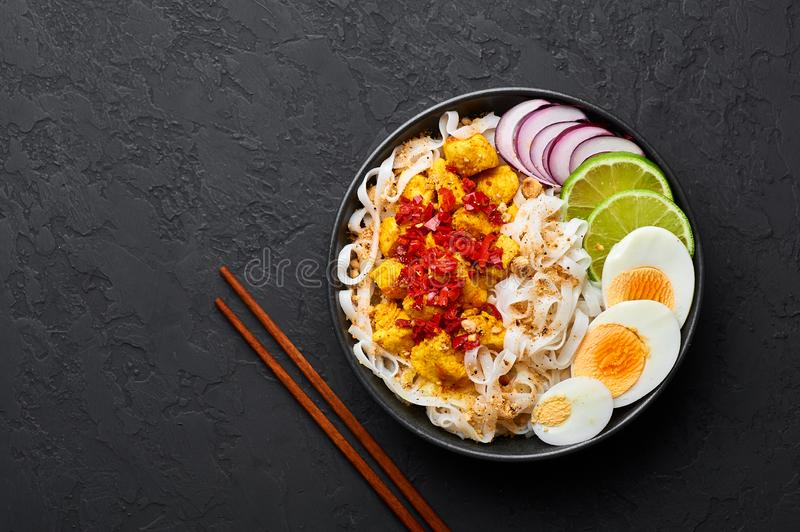 Nan Gyi Thoke in black bowl at dark slate background. Nan gyi Thohk is popular burmese cuisine dish. With rice noodles, chicken breasts with spices, eggs stock photos