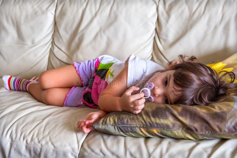 Nana medio dormida del sofá de la hora de acostarse del sofá del niño del bebé de la siesta de la tarde imagenes de archivo