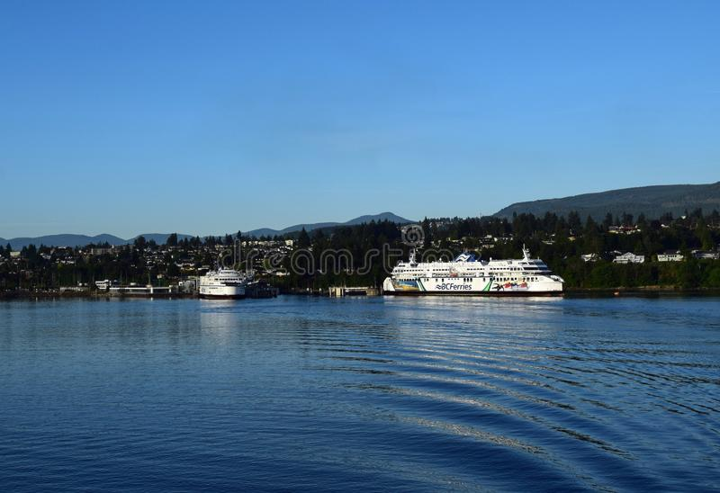 Ferries moored in Nanaimo British Columbia. Nanaimo, BC Canada - 17 Jun, 2019: two BC ferries moored at the pier seen from the ocean with the city in the royalty free stock photography