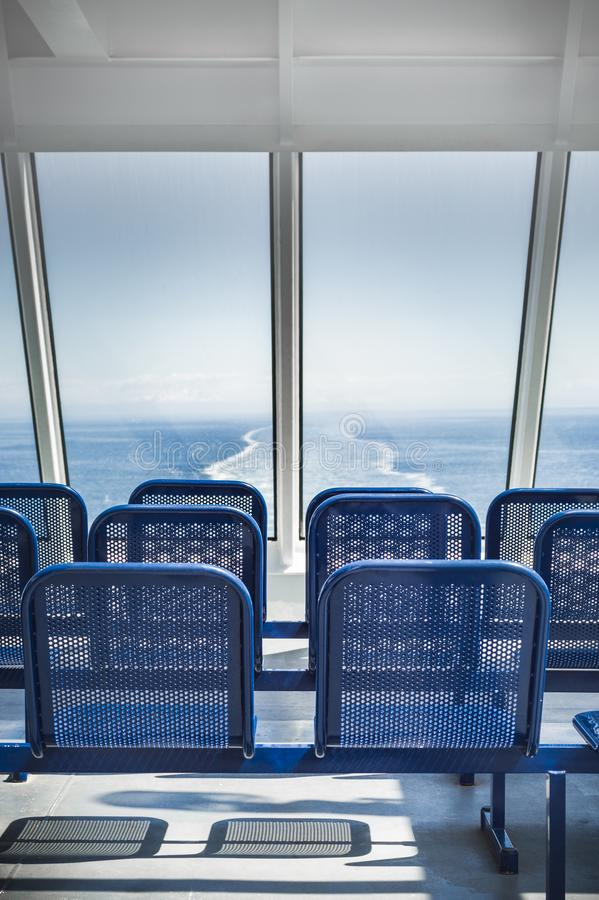 Empty blue metal ferry ship seats in facing the ocean. NANAIMO, BC, CANADA - MAY 27, 2017: Outdoor seats and Eastward view of clear blue sky and Strait of royalty free stock images