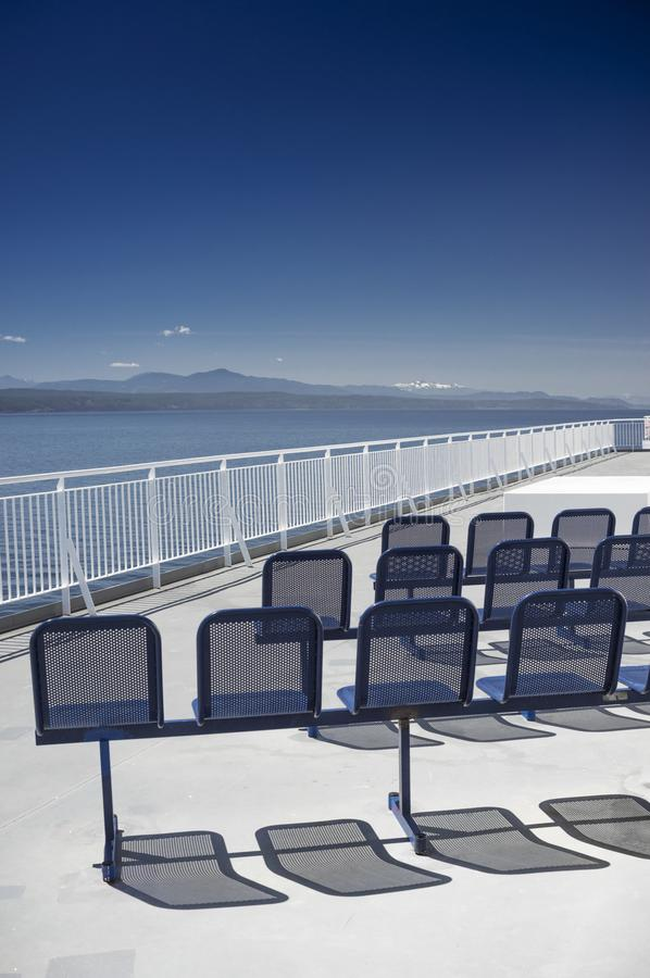 Empty blue metal ferry ship seats in sunshine. NANAIMO, BC, CANADA - MAY 27, 2017: Outdoor seats and Western view of clear blue sky and Strait of Georgia from royalty free stock image