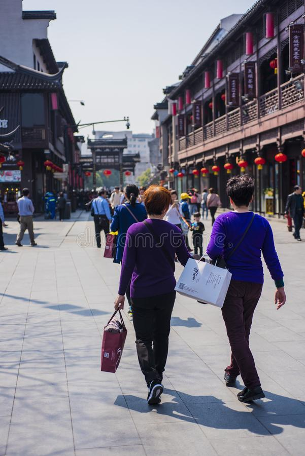 Two women in purple blouses pass by temple square. Nanjing fuzi temple square, jiangsu province. Two women in a purple tunic and carrying shopping bags pass stock photos