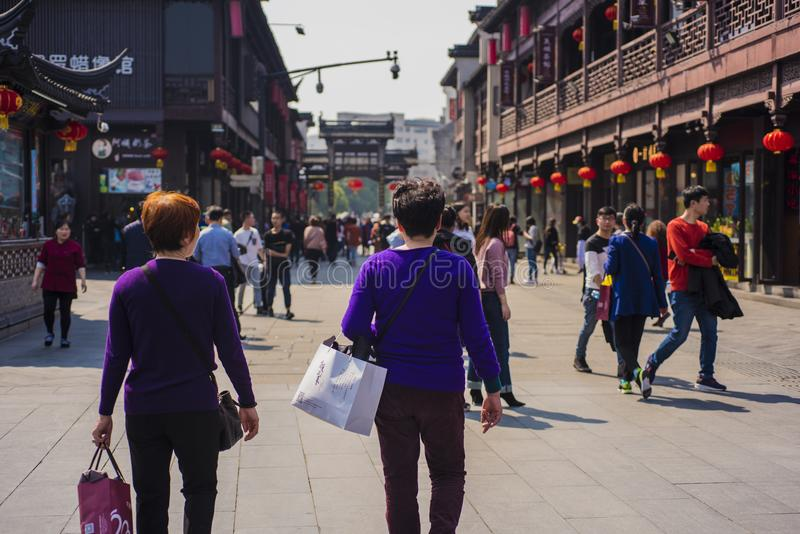 Two women in purple blouses pass by temple square. Nanjing fuzi temple square, jiangsu province. Two women in a purple tunic and carrying shopping bags pass royalty free stock images