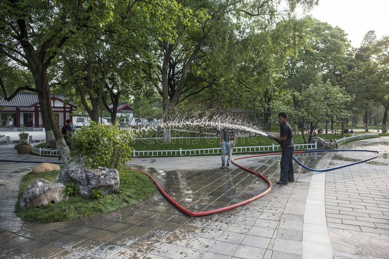 Garden workers watering flowers in Xuanwu Lake Park royalty free stock images