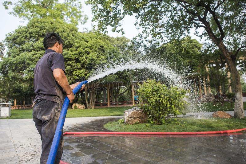 Garden workers watering flowers in Xuanwu Lake Park stock photography