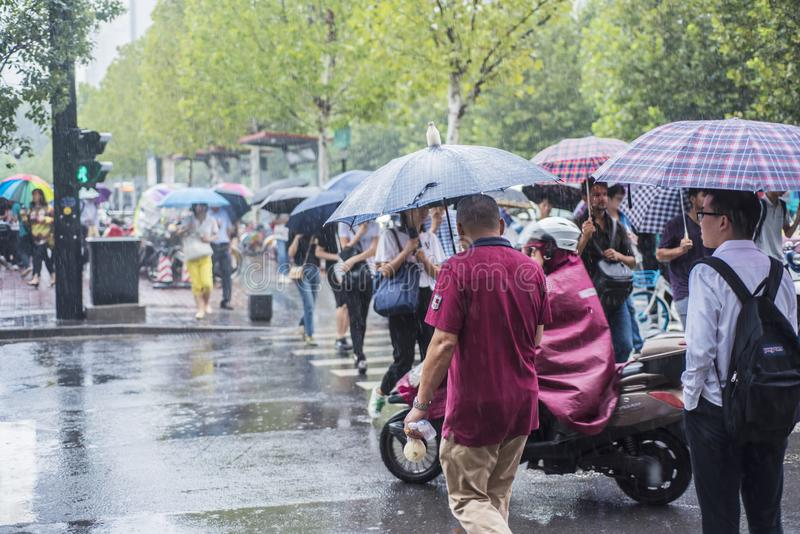 A rain in the morning, people going to work crossed the intersection with an umbrella. Nanjing, Jiangsu, Changfu Street subway exit, a heavy rain in the morning
