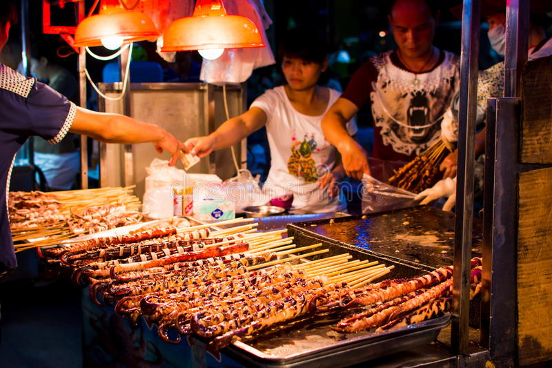 NANNING, CHINA - JUNE 9, 2017: Food on the Zhongshan Snack Street, a food market in Nanning with many people bying food and royalty free stock images