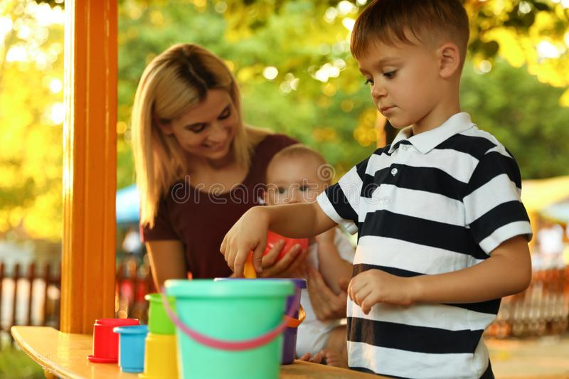 Nanny and cute children playing with toys. Outdoors stock photo