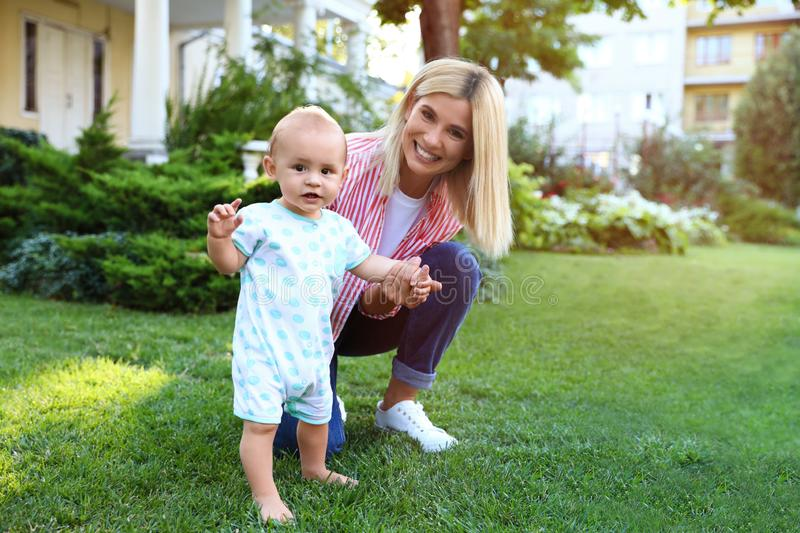 Nanny with cute little baby on green outdoors royalty free stock image