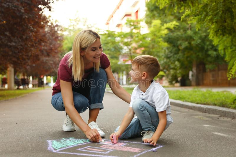 Nanny with cute little boy drawing house with chalks. On asphalt stock image