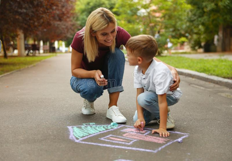Nanny with cute little boy drawing house with chalks royalty free stock image