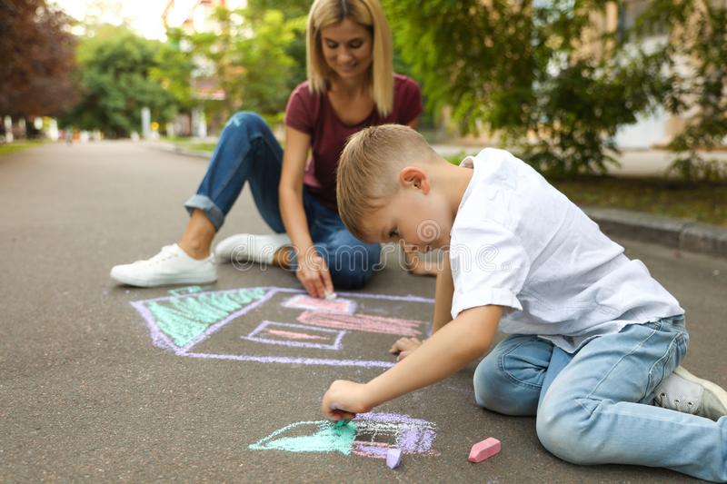 Nanny with cute little boy drawing house with chalks royalty free stock photos