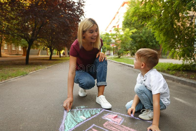 Nanny with cute little boy drawing  with chalks on asphalt stock photos